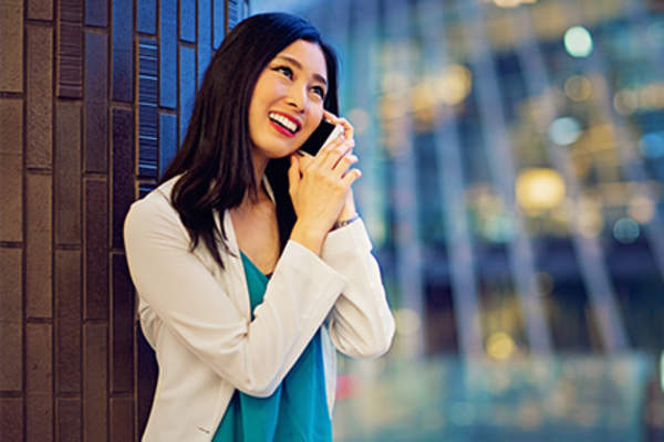 Smiling woman talking on cellphone outside of office.