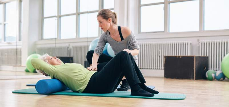 older woman exercising with trainer