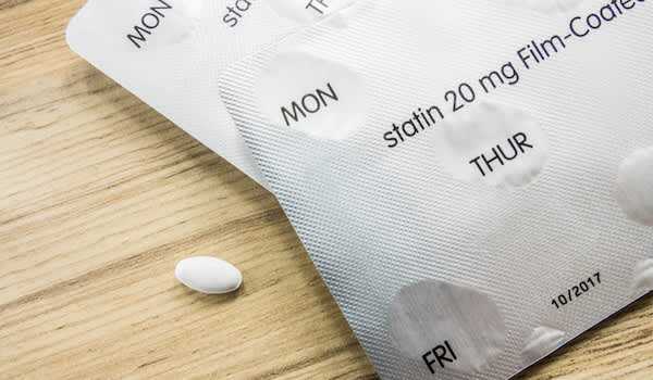 Statin pill and blister packs on table.