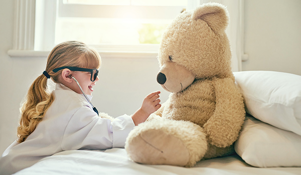 Young girl using stethoscope to play doctor with teddy bear.