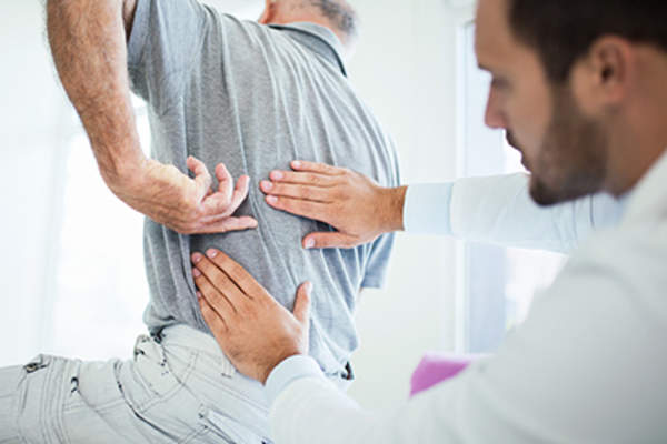 Doctor assessing a patient's back pain.