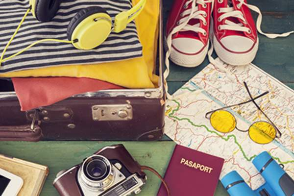 Packing suitcase with passport, camera, clothing, and map