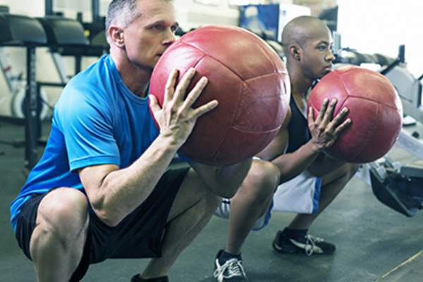 Men doing ball exercises at the gym.