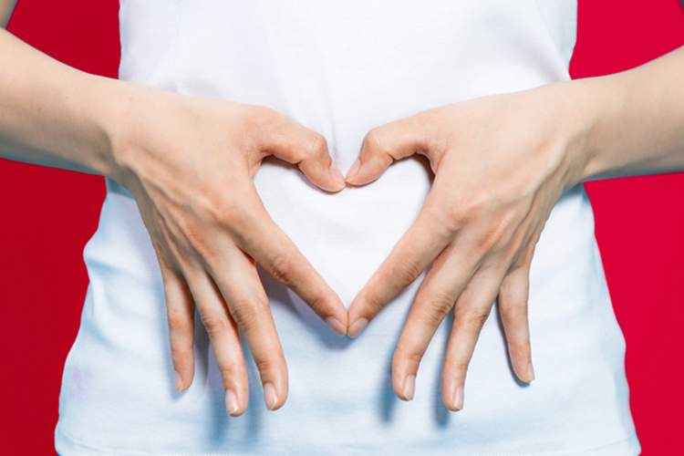 Woman making heart with hands over her GI tract showing digestive health.