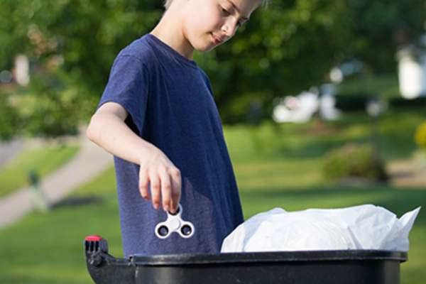 Teen boy throwing away fidget spinner.