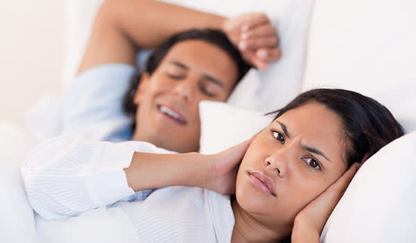 Young woman cannot sleep, partners snoring.