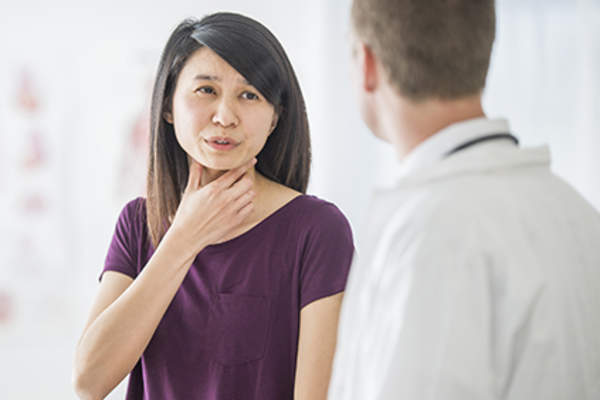 Woman discussing throat pain with her doctor.