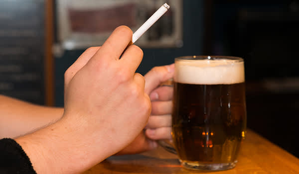 Man having cigarette and beer.