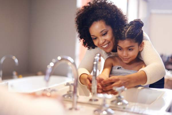 Mother shows daughter how to properly wash her hands.