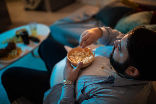 Overweight man sitting on couch watching TV and eating popcorn
