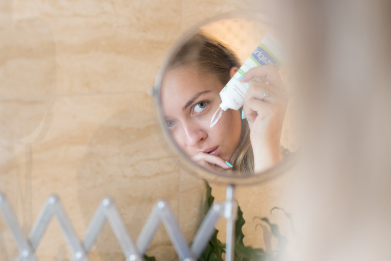 woman putting cream on in mirror