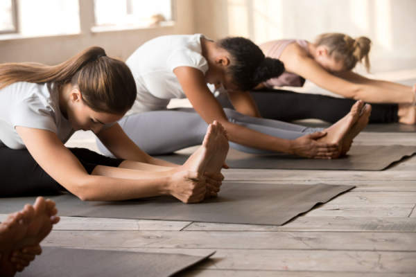 yoga class doing forward fold