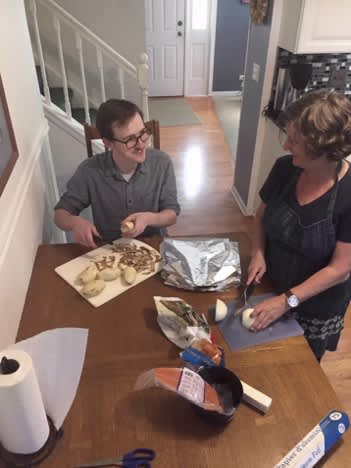 Cathy and her son prepping the ingredients to throw in their foil packets.