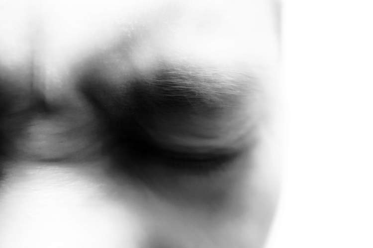 black and white blurred close up of eyes squinting in pain