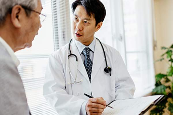 Male doctor showing record to senior patient