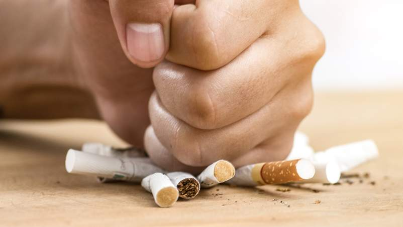 Close up of fist crushing cigarettes, stop smoking concept.