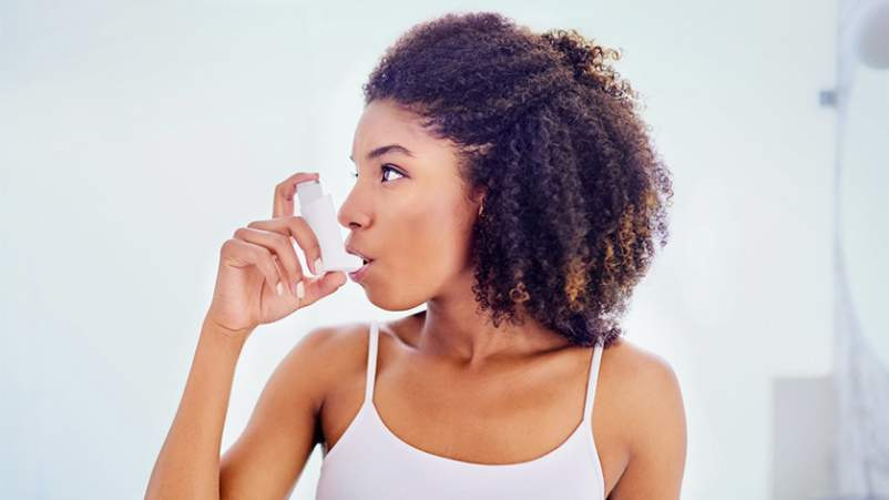 Young woman using an inhaler for asthma.