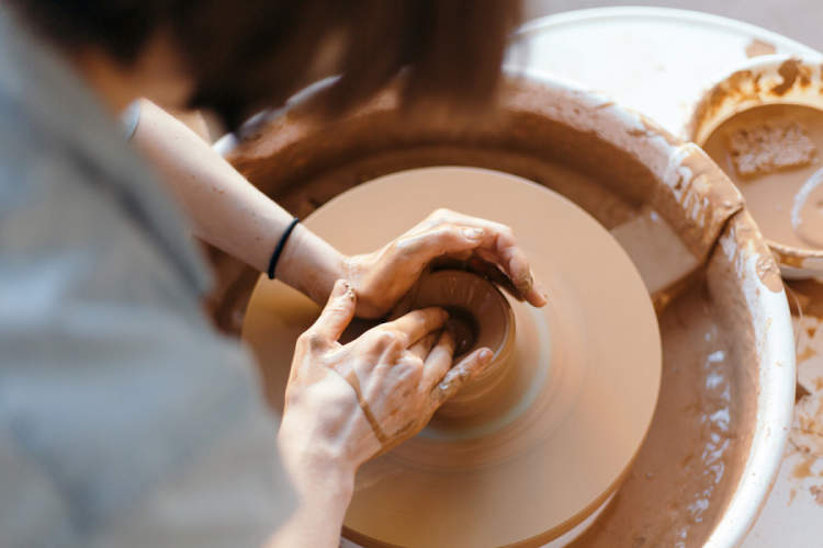 woman's hands making pottery on wheel