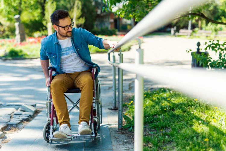 young man in manual wheelchair going up ramp