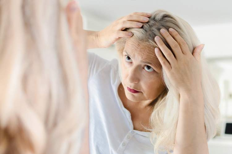 Woman examining her scalp in the mirror.
