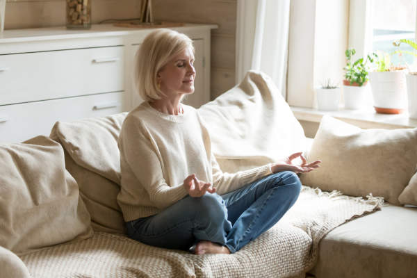 Senior woman meditating in living room