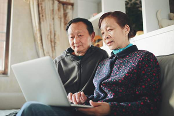 Senior Asian couple on laptop at home.