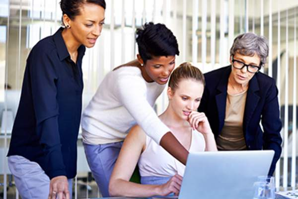 Businesswomen gathered around a laptop.