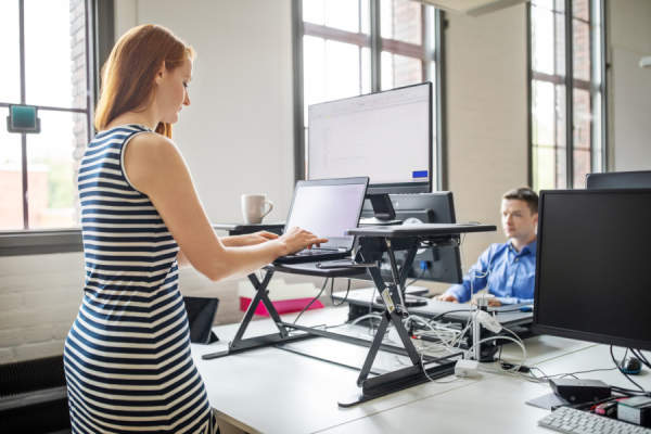 Businesswoman working at ergonomic standing desk