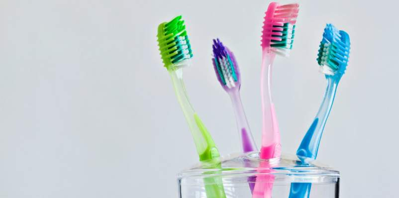 colored toothbrushes in holder cup