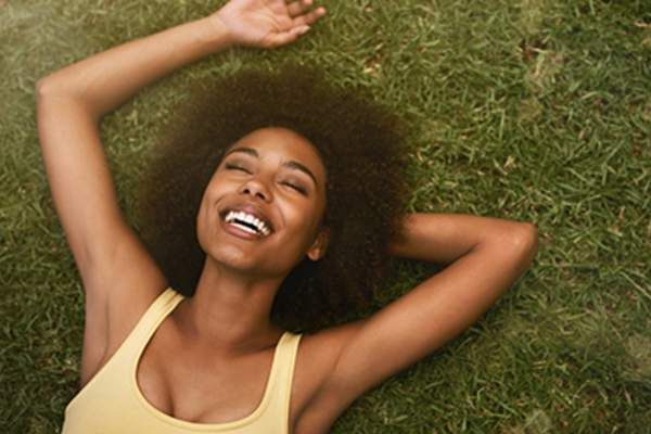 Woman laughing while laying in the grass.