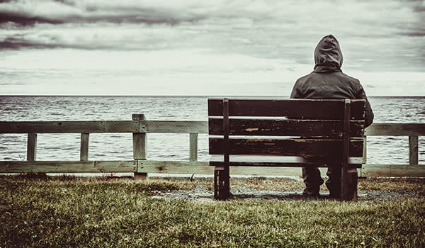 Lonely man sitting on a bench near the sea.