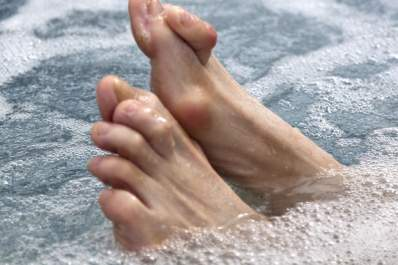Feet with hammertoe sticking up from a bathtub.