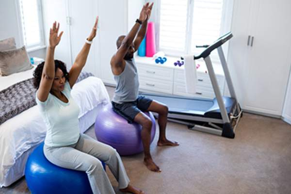 Couple exercising on stability balls in bedroom
