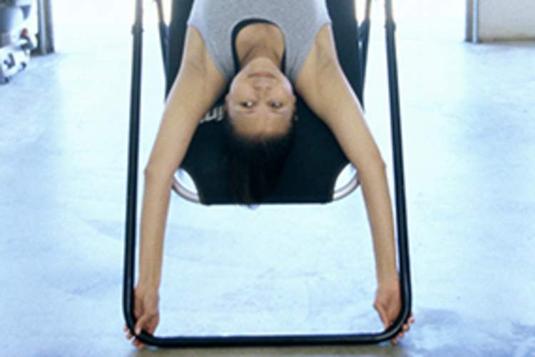 A woman does inversion therapy for a spinal condition.