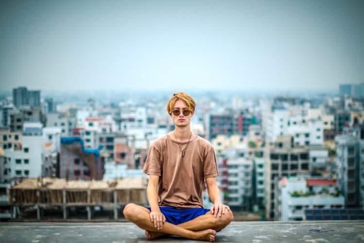man meditating on roof