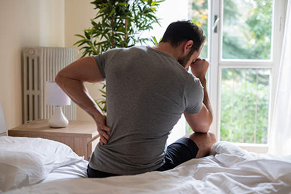 Man's back pain worsened by lack of sleep.