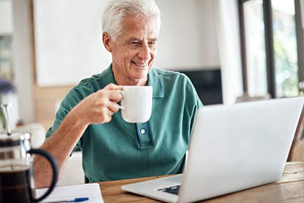 Smiling man holding coffee while on laptop at home.