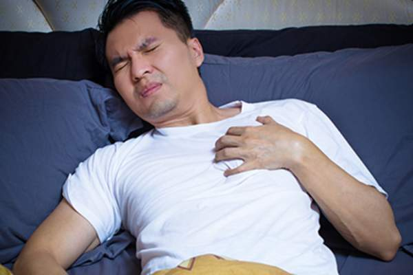 Man having chest pain in bed.