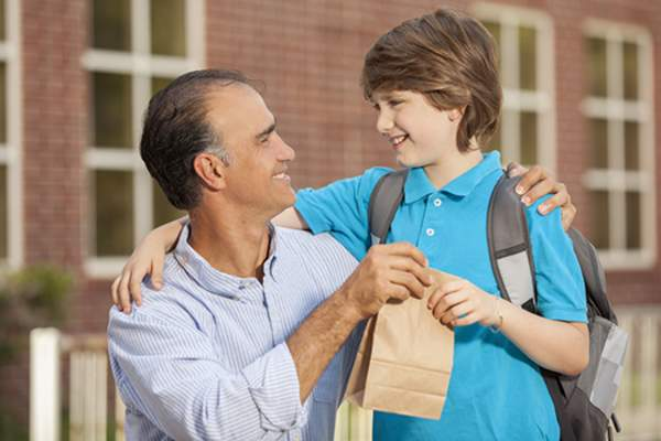 Dad giving son bagged school lunch.