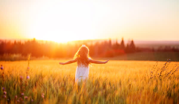 Young girl in field at sunset.