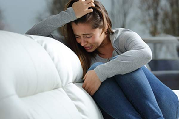 Woman crying on a couch.