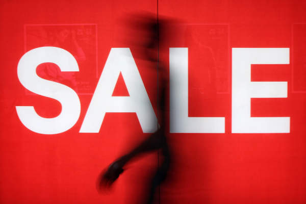 person walking past sale sign