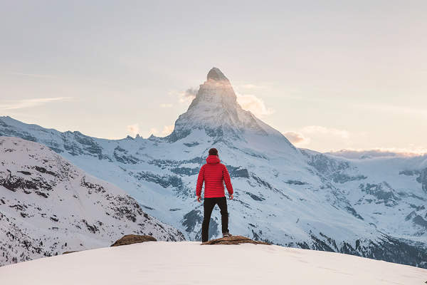 Man in red jacket standing in snow looking at distant mountain