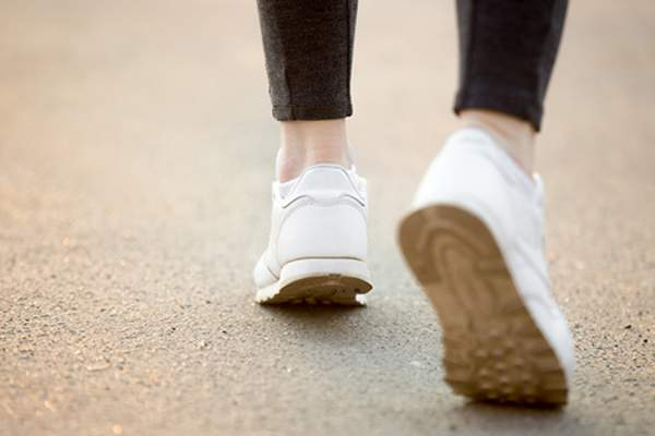 Close-up of woman's feet walking in sneak