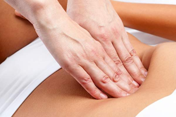 Therapist's hands pressing on female abdomen.