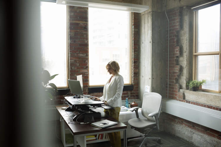 Woman working at standing desk.