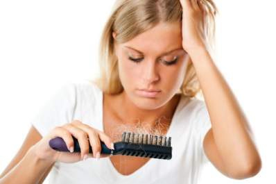 Woman staring at all the hair caught in her brush.