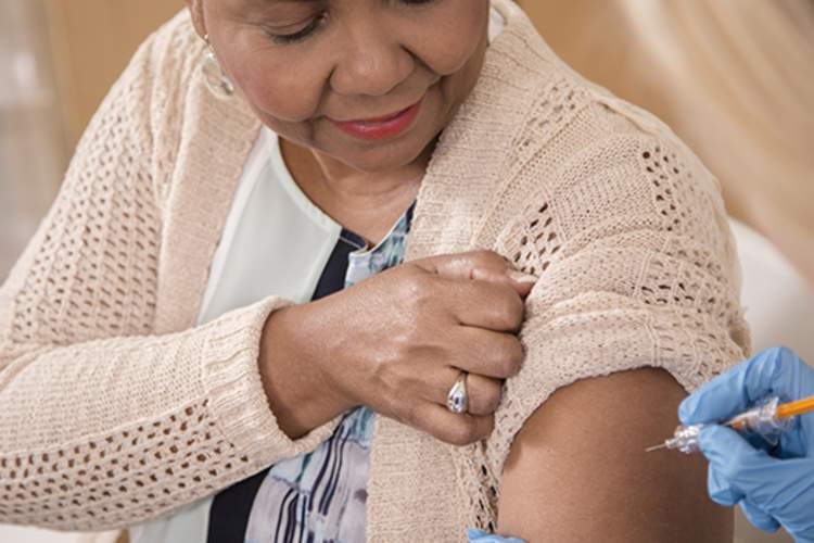 Nurse gives flu vaccine to senior adult patient at clinic