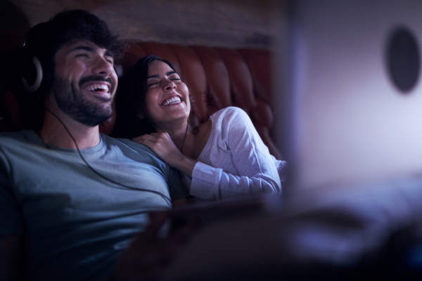 couple laughing and watching movie on laptop