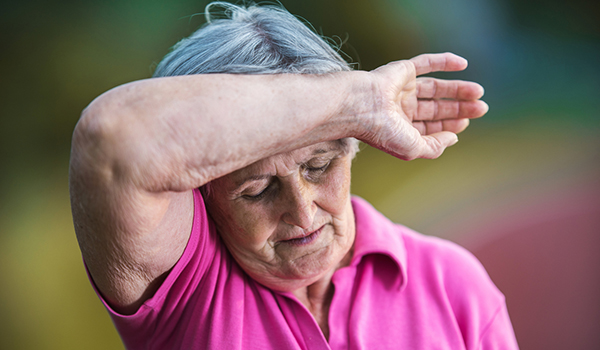 Senior woman sweating with arm on forehead.